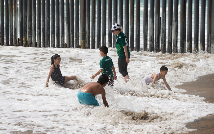 A family plays in the surf alongside the Mexico - U.S. border fence at El Faro Park on the Mexican side of the border. Photo by Mike DuBose, UMNS.