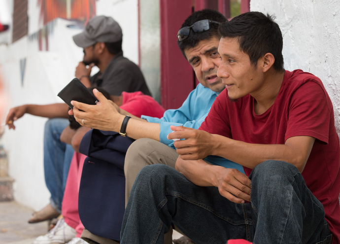 The Rev. Joel Hortiales (center) visits with Elias from the Mexican state of Chiapas outside the Border Angels shelter for migrants in Tijuana. Photo by Mike DuBose, UMNS.