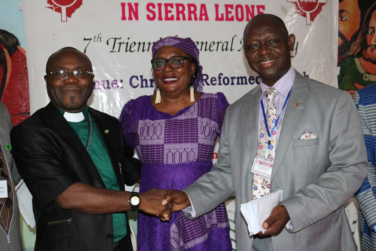 Bishop John Yambasu (right) is congratulated by Ebun James Dekam (center) and the Rev. Bob Williams after Yambasu was elected president of the Council of Churches in Sierra Leone for a second term during the council's conference in Kabala, Sierra Leone. Dekam is general secretary of the council and Williams is a United Methodist pastor. Photo by Phileas Jusu, UMNS.