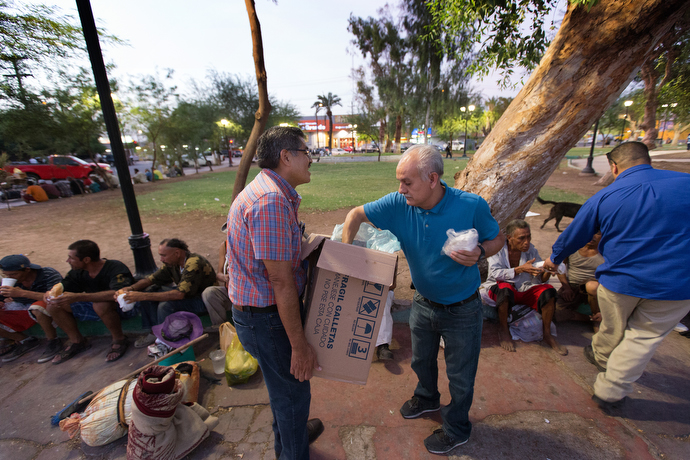 Bishop Felipe Ruiz Aguilar of the Methodist Church of Mexico (holding box) and Victor Rodriguez of El Divino Redentor Methodist Church help serve dinner to migrants and others living on the street at Mariachi Plaza. Photo by Mike DuBose, UMNS.