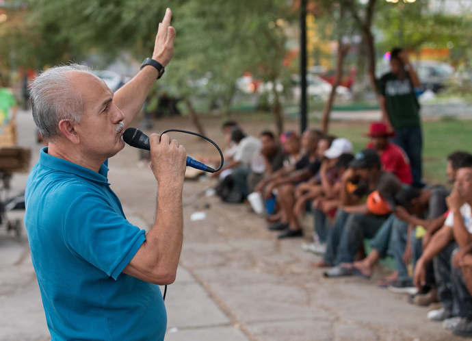 Victor Rodriguez shares his own story of homelessness and addiction with migrants and others living on the street during a dinner and worship service at Mariachi Plaza. Photo by Mike DuBose, UMNS.