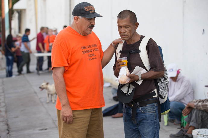 Javier Trejo (left) from La Santísima Trinidad Methodist Church offers breakfast and a prayer to Candalario Tapia who is living on the street in Mexicali.