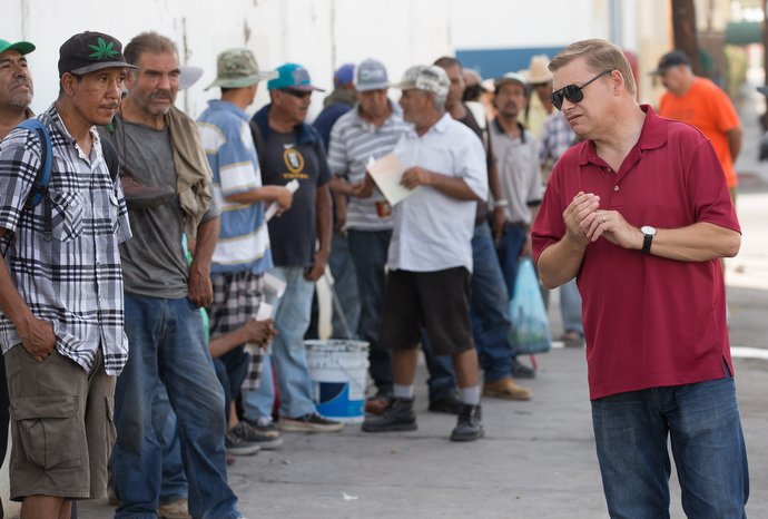 The Rev. Jacob Van Der Schaaf (center) and Elly Rodiles (right) from La Santísima Trinidad Methodist Church offers breakfast and a prayer to Jesus Perez in Mexicali. Photo by Mike DuBose, UMNS.