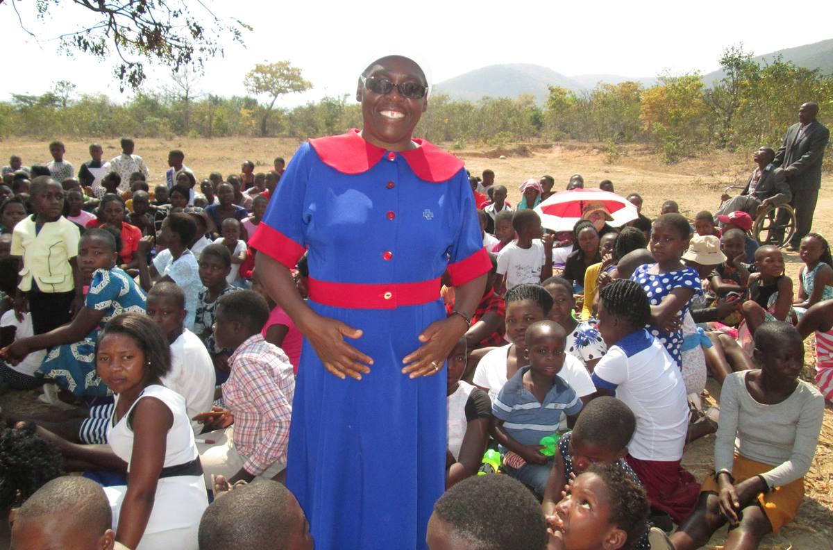 Rebecca Tendai Gurupira, speaker during an outreach program against violence and childhood marriages in Zimbabwe, stands surrounded by young people at the Nyambeya Camping site in the Chimanimani District.  Photo by Kudzai Chingwe, UMNS.