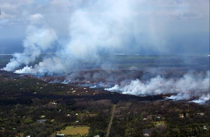 This aerial view shows plumes of smoke and volcanic gas caused by lava moving into residential areas in the Leilani Districts, Hilo, Hawaii. Photo by Pfc. Trevor Rowell, U.S. Marine Corps.