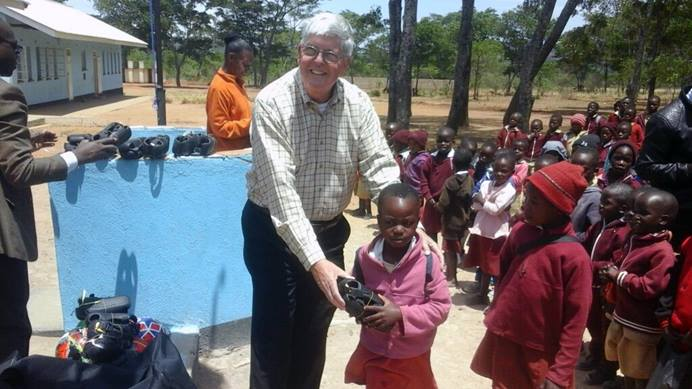 Charlie Moore, a member of Community United Methodist Church in Crofton, Maryland, and team leader of the Zimbabwe Volunteers in Mission, hands shoes to a student at Hanwa Mission School in Zimbabwe. For over 20 years, the U.S. church has been working with United Methodists in the Zimbabwe West Conference to improve lives in the rural Murewa District. Photo by Chenayi Kumuterera, UMNS.