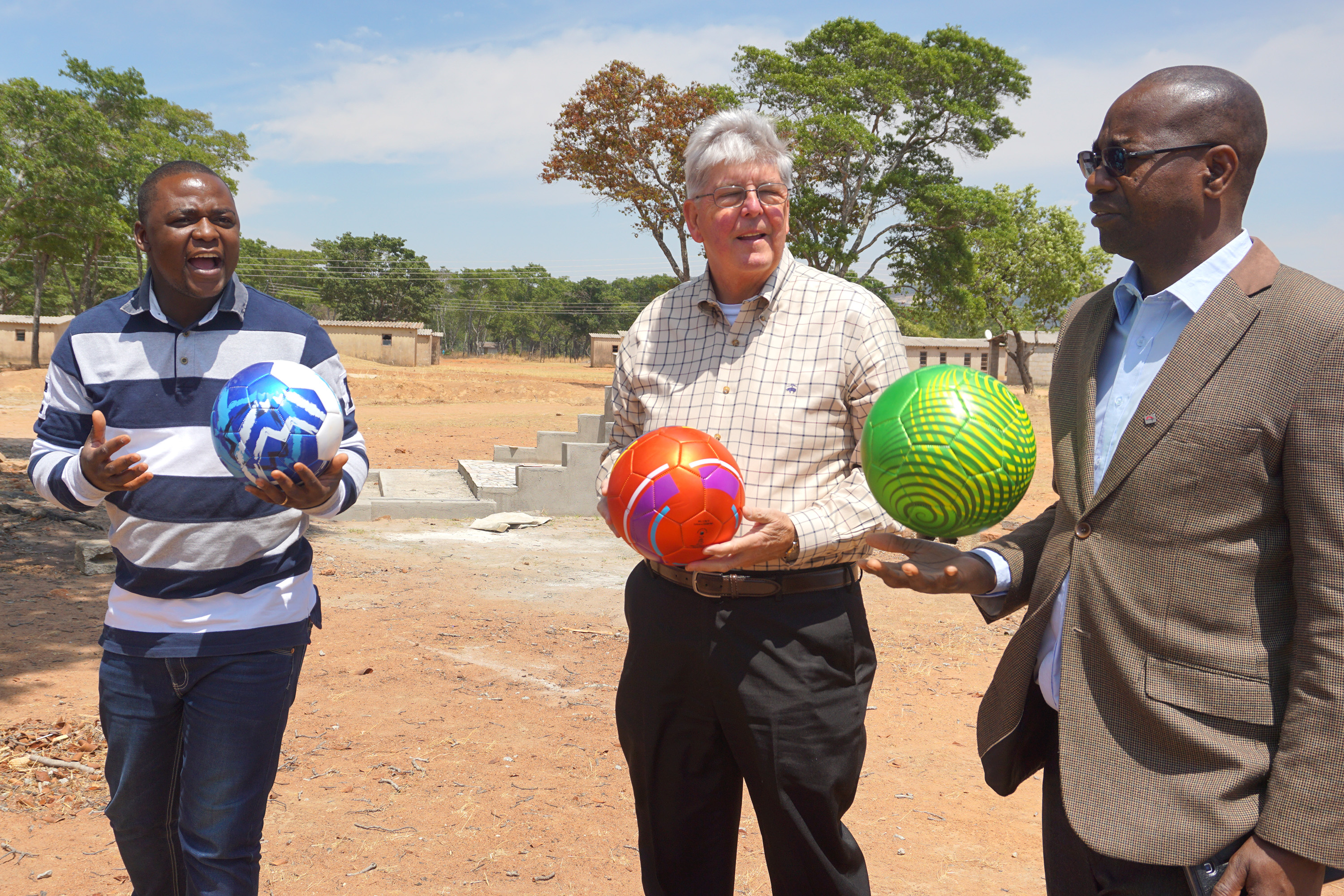 The Rev. Future Sibanda, left, Charlie Moore and the Rev. Henry Luckson Chareka hold soccer balls donated to students at Hanwa Mission School in the Murewa District of Zimbawe as part of a partnership between Community United Methodist Church in Crofton, Maryland, and United Methodists in the Zimbabwe West Conference. Photo by Chenayi Kumuterera, UMNS.