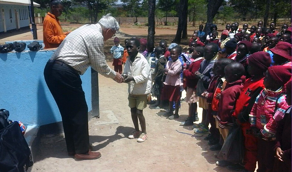 Charlie Moore hands a pair of shoes to a student at Hanwa Mission School in the Murewa District  of Zimbabwe. Moore brought 50 pairs of shoes and a dozen soccer balls to hand out to the students as part of a partnership between Community United Methodist Church in Crofton, Maryland, and the Zimbabwe West Conference. A fifth-grade class from Crofton Elementary in Maryland donated the items. Photo by Chenayi Kumuterera, UMNS.