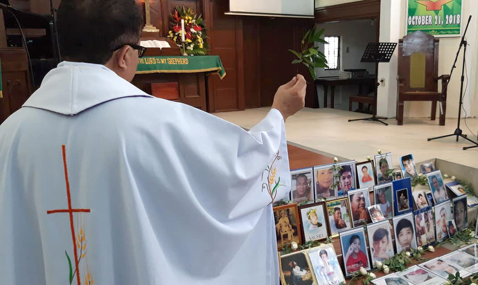 The Rev. Nonie Aviso of the United Church of Christ in the Philippines blesses photos of the victims of drug-related violence during a service at St. Paul United Methodist Church in Manila. Photo courtesy of Juliet Solis.