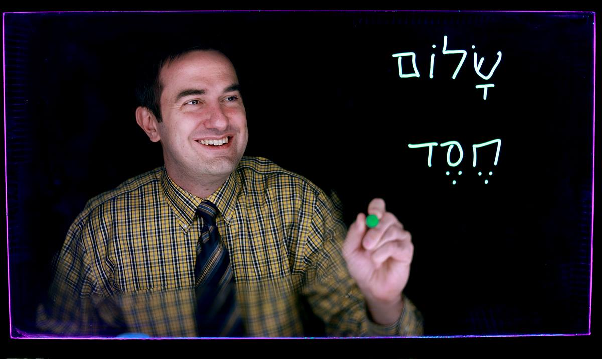 "The Rev. Matthew Richard Schlimm, author of ""70 Hebrew Words Every Christian Should Know,"" uses a light board to write two Hebrew words. At top is the word that transliterates to ""shalom,"" meaning ""peace"" or ""well-being."" The bottom word is ""khesed,"" meaning ""love"" or ""loyalty."" Schlimm is a United Methodist elder and professor of Old Testament at the University of Dubuque Theological Seminary. Photo by Nick Story, the University of Dubuque."