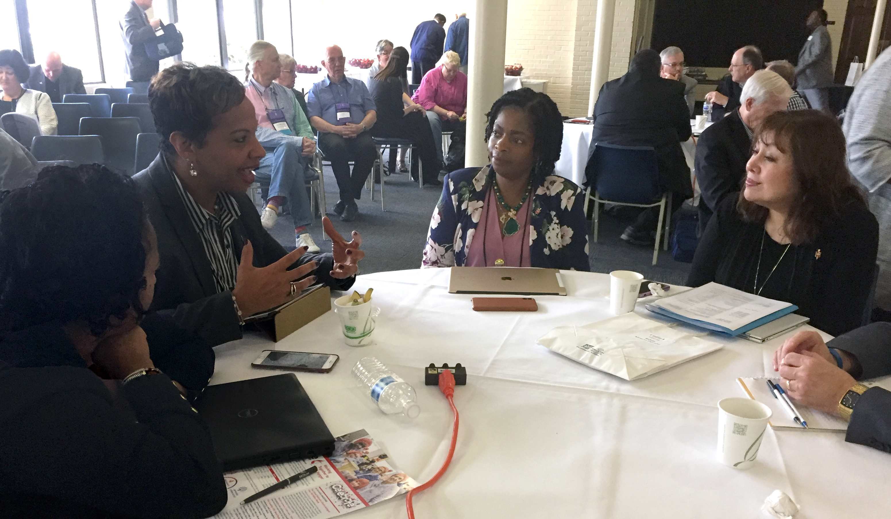 Bishops gather in small groups to discuss what scriptural imagination means in this uncertain season in the church. From left are Bishops Sharma Lewis, Tracy Smith Malone (speaking), Cynthia Moore-Koikoi and Minerva Carcaño. Photo by Heather Hahn, UMNS.