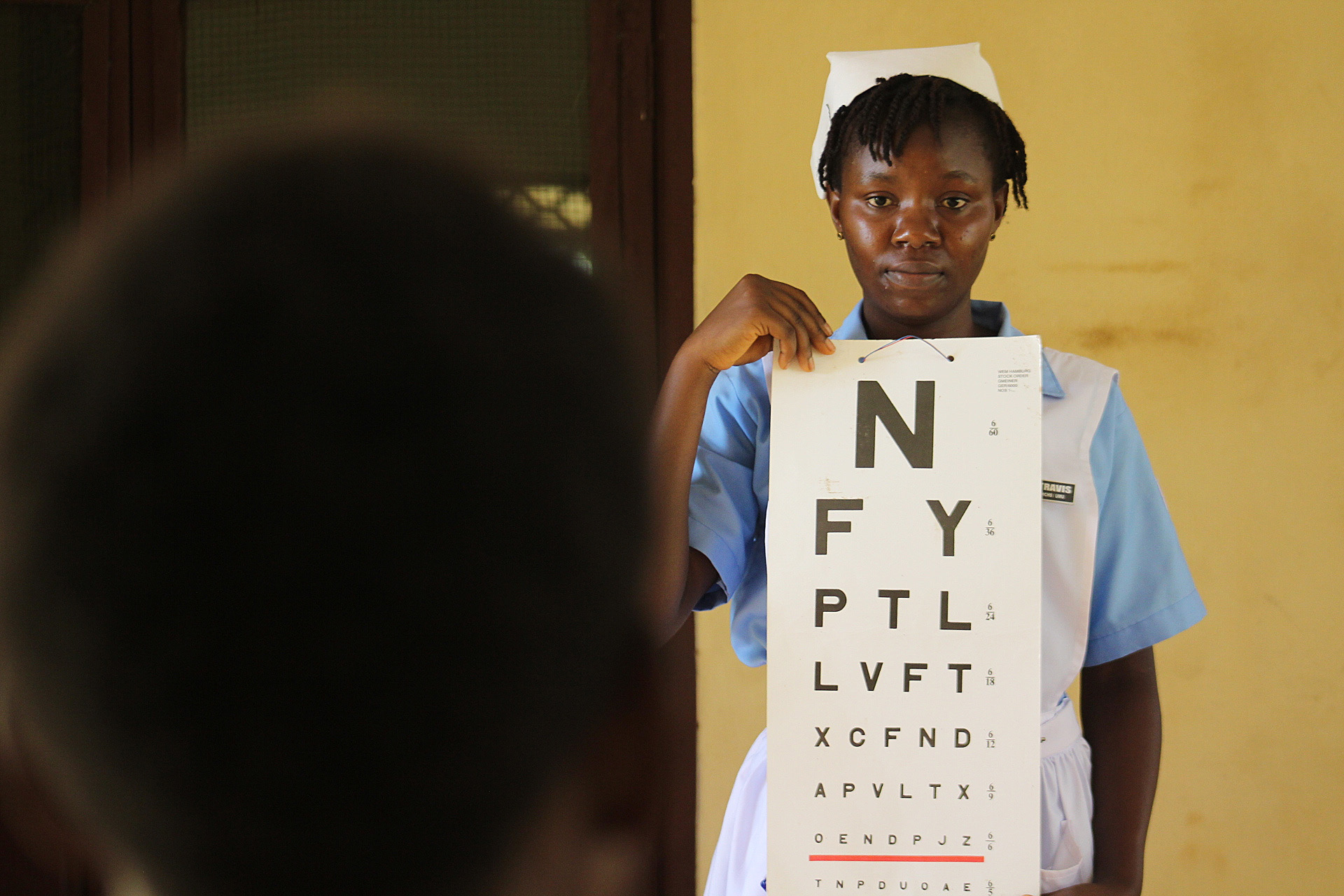 John Togba from the Jorquelleh District takes an eye screening test at Ganta Hospital in Nimba County, Liberia. Photo by E Julu Swen, UMNS.