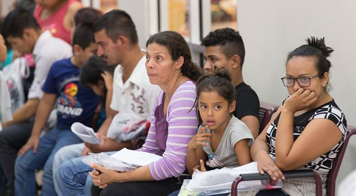 Immigrants who have just been released from a U.S. Border Patrol detention facility wait at the bus station in McAllen, Texas, in this photo from Aug. 1. Photo by Mike DuBose, UMNS.