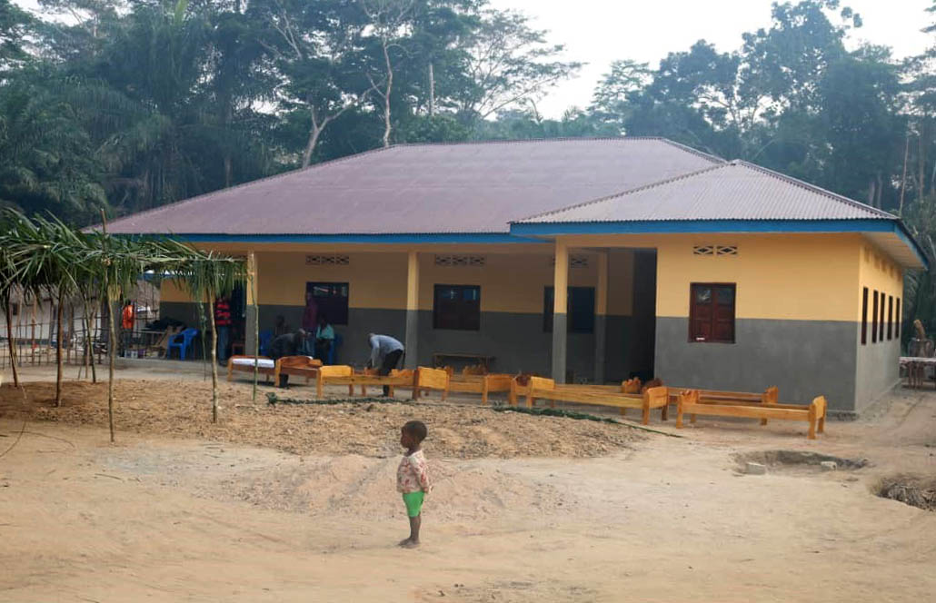 A young child stands outside the new Okasa Medical Center located in a village outside Kibombo, Congo. The center was built with support from the denomination's Imagine No Malaria program. Photo by Chadrack Tambwe Londe, UMNS