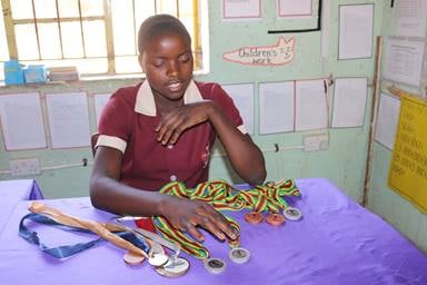 13-year-old Ngaakudzwe Katsvairo displays her medals from both local and international track and field competitions. Katsvairo attends The United Methodist Church's Mashambanhaka Central Primary School in Zimbabwe. Photo by Eveline Chikwanah, UMNS.