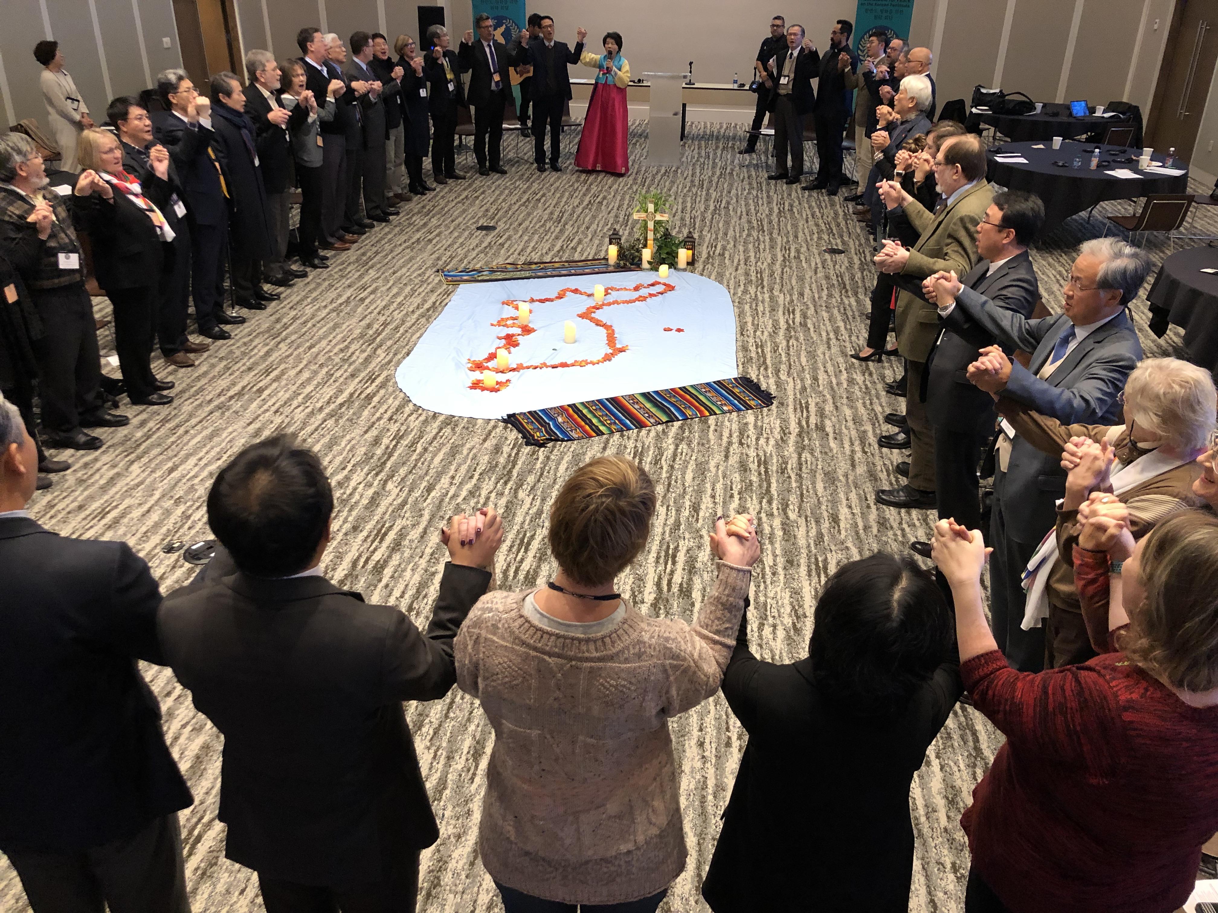 한반도 평화를 위한 원탁 회담에 참석자들이 주일 예배 중 손에 손을 잡고 찬송을 하고 있다. 사진 김응선 목사, UMNS