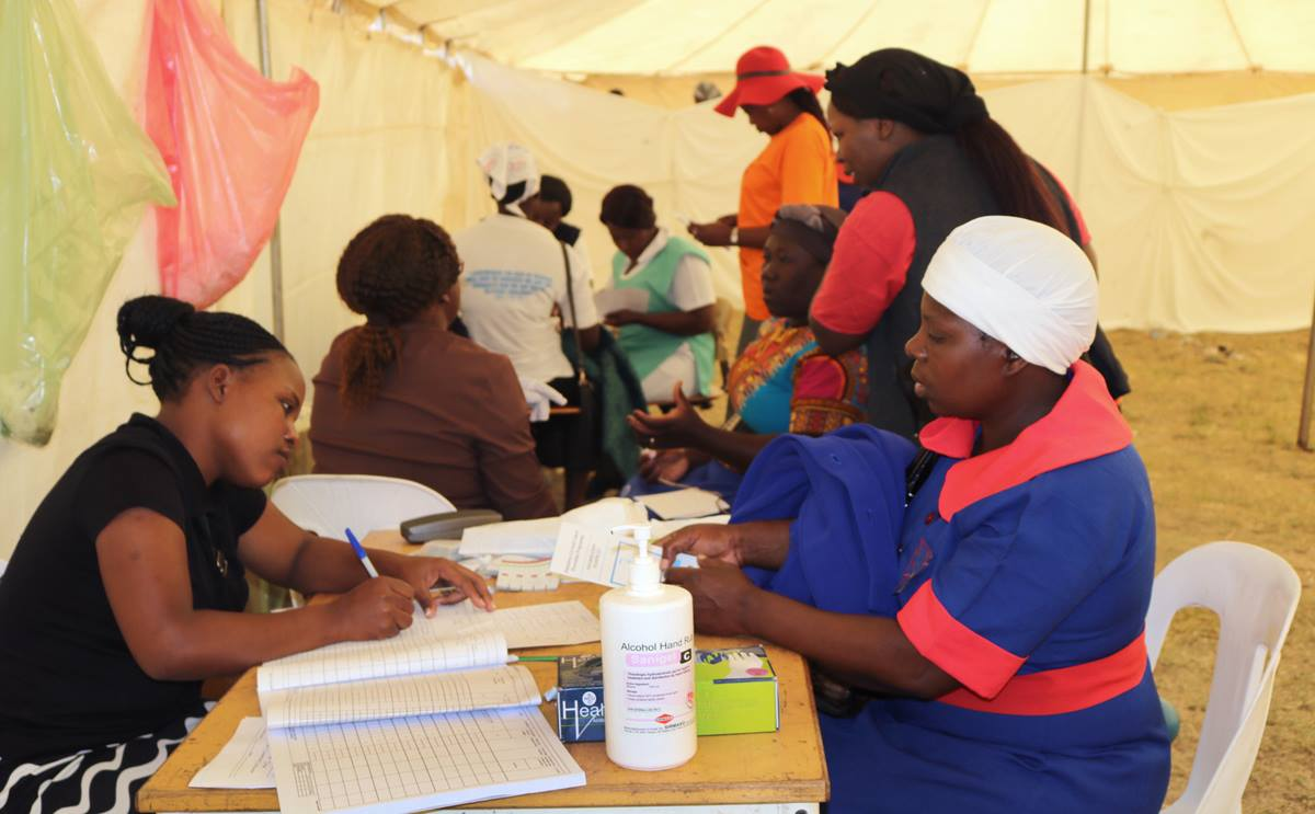 Women check in at registration desks before entering private bays for testing. Over 400 women were screened for cervical cancer during the annual women's convention at Clare Camping Ground in Rusape, Zimbabwe. Photo by Eveline Chikwanah, UMNS.
