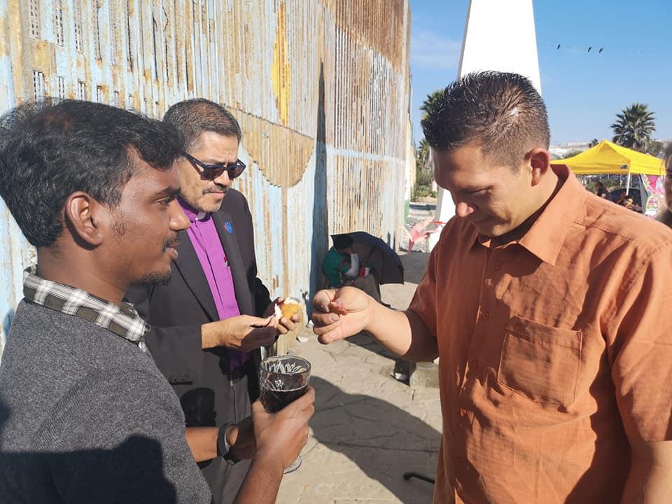Bishop Felipe Ruiz-Aguilar (center) and United Methodist Global Ministries missionary Yabes Manokaran (left) share communion with migrants during a worship service at El Faro: The Border Church. Photo by Misael Ruiz Lara, Methodist Church of Mexico.