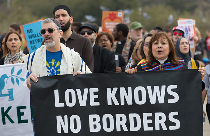 United Methodist Bishop Minerva Carcaño (right) and Rabbi Brant Rosen help lead a multifaith march in support of justice for migrants at Border Field State Park In San Diego. Photo by Mike DuBose, UMNS.
