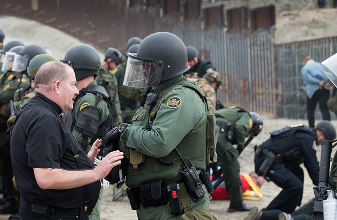 The Rev. Rolly Loomis, pastor of First United Methodist Church of Roseville, Calif., is detained by a U.S. Border Patrol agent at the fence between the U.S. and Mexico in San Diego. Loomis joined with other faith leaders in attempting to offer a ceremonial blessing in support of migrants seeking refuge in the U.S. Photo by Mike DuBose, UMNS.