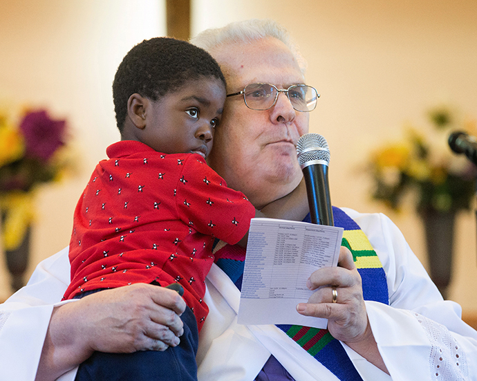 The Rev. Bill Jenkins, gives the sermon during worship at Exodus United Methodist Church in San Diego while holding his foster son Harry, who is from Haiti. The church is the only immigrant-welcoming center in Southern California. Photo by Mike DuBose, UMNS.