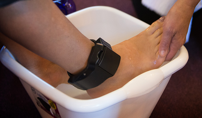 A migrant from Central America, wearing a tracking device on her ankle while she pursues an asylum claim in the U.S., has her feet washed during worship at Exodus United Methodist Church in San Diego. Photo by Mike DuBose, UMNS.