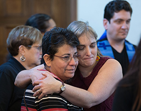 The Rev. Patricia Gandarilla (front, left) of El Buen Pastor United Methodist Church in Detroit and Lori Valentine de Segovia of the Virginia Conference embrace during a migration-themed worship service at Exodus United Methodist Church in San Diego. Photo by Mike DuBose, UMNS.