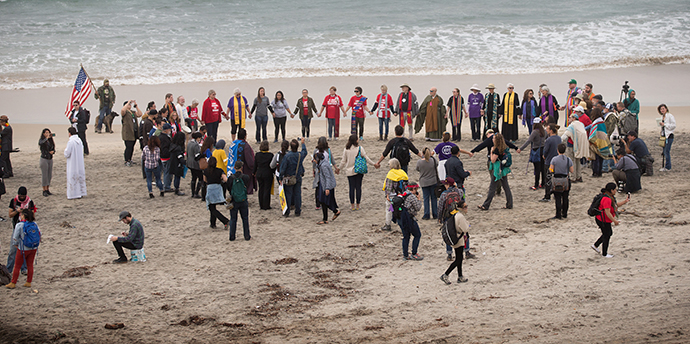 Faith leaders and supporters of immigrant rights gather in prayer on the beach near the U.S. Mexico border in support of migrants seeking refuge in the U.S. Photo by Mike DuBose, UMNS.