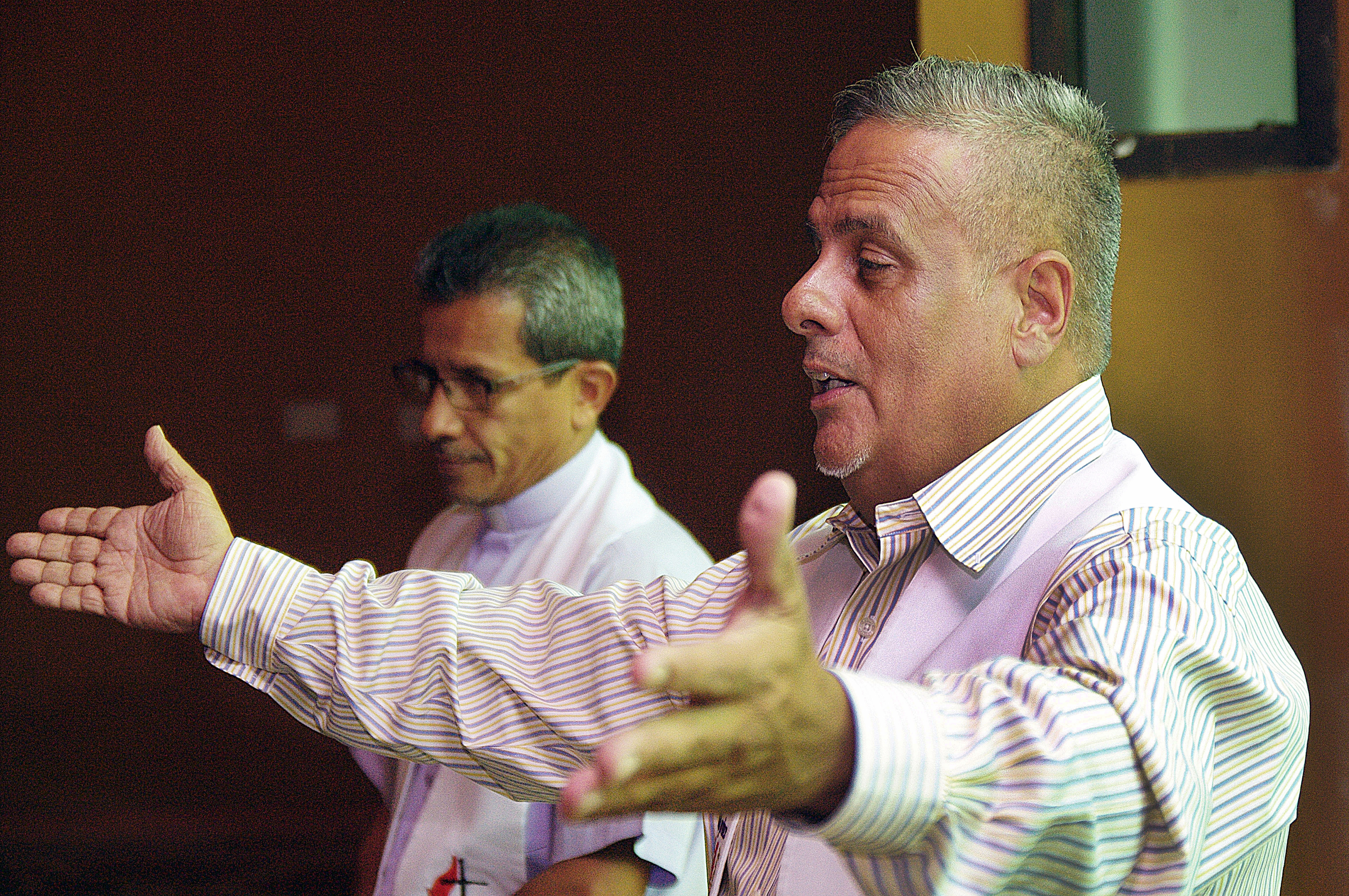 Pastor Fernando Mendez, Christian Methodist Community of Venezuela, right, and Bishop Toby Ramirez, Council of Evangelical Methodist Churches of Venezuela, presided together during the sacrament of communion, which served as a symbol of the spirit of unity that reigned during a dialogue about establishing a national Methodist church presence in Venezuela. Photo by Gustavo Vasquez, UMNS.
