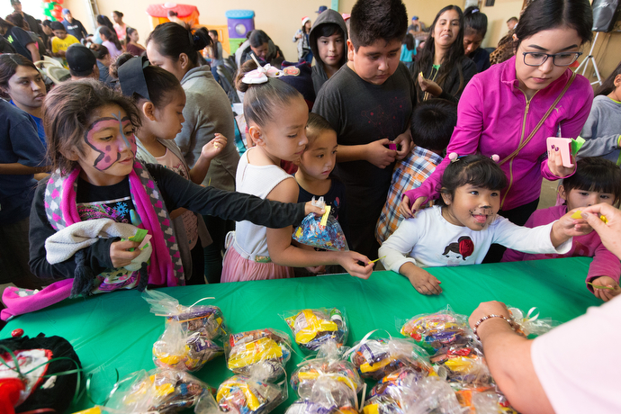 Children line up for treat bags at the Christmas party.