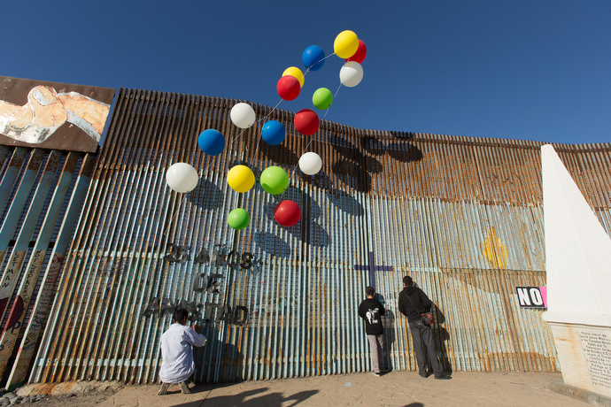 During a Posada celebration at El Faro Park in Mexico, people peer through the border fence that separates the U.S. from Mexico while a volunteer affixes a sign celebrating the 25th anniversary of La Posada Without Borders.
