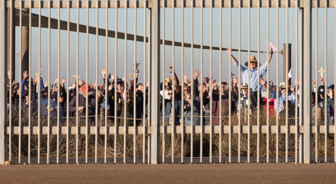 United Methodist pastor John Fanestil (standing above crowd at right) leads participants in a Posada celebration on the U.S. side of a secondary border fence that separates San Diego from Tijuana, Mexico. On the 25th anniversary of La Posada Without Borders, Friendship Park was closed on the U.S. side while hundreds gathered freely on the Mexico side.