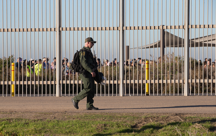 A U.S. Border Patrol agent walks through Friendship Park in San Diego, between the primary and secondary border fences that separate the U.S. from Mexico, during the 25th anniversary of La Posada Without Borders.
