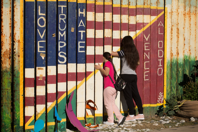 During a Posada celebration at El Faro Park in Tijuana, Mexico, people peer through a section of the U.S.-Mexico border fence that is decorated with a message of love in two languages.