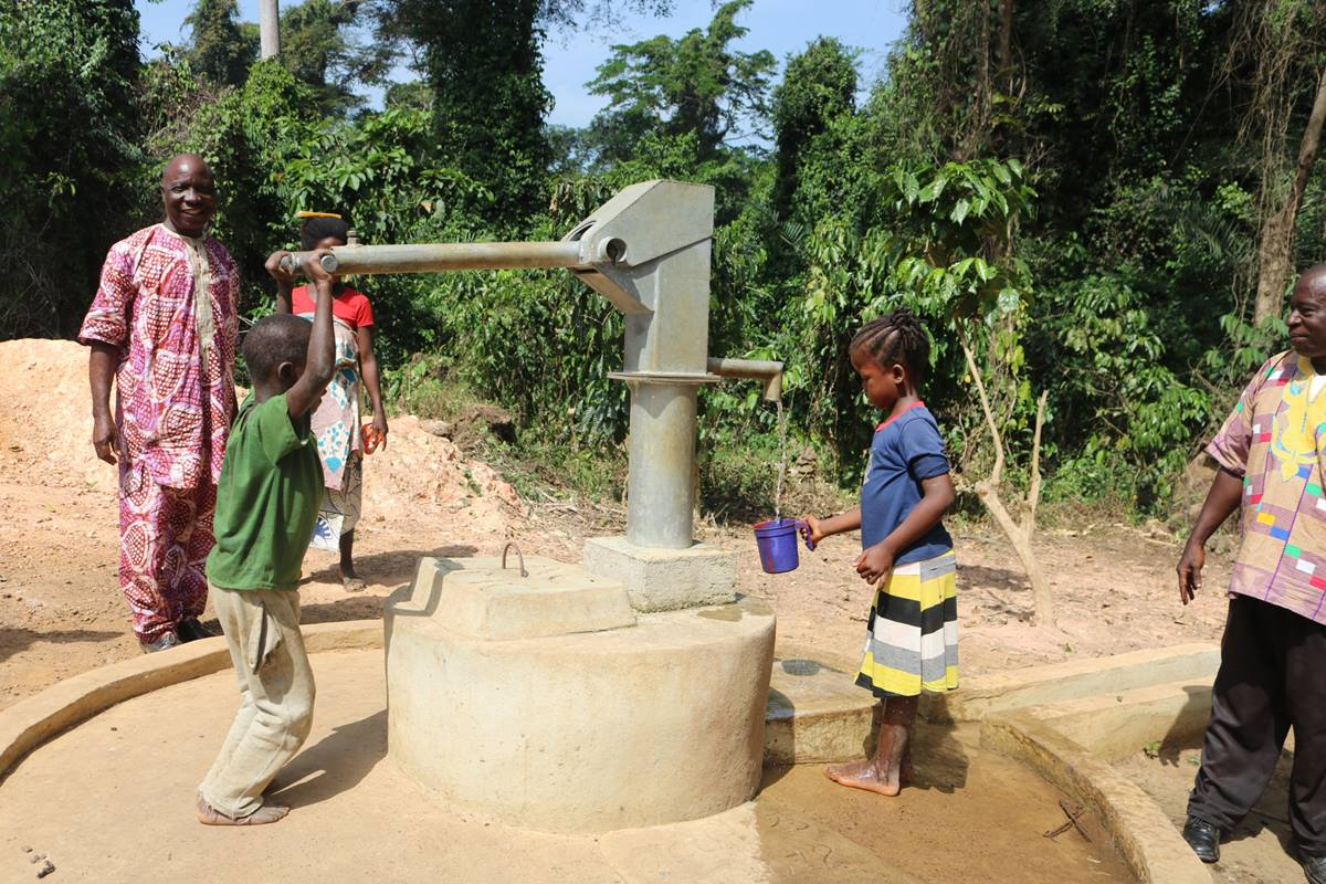 Dolo Boamou and Denise Kpoghomou pump water from a well as adults look on in Yassata, Guinea. The United Methodist Church in Liberia is building five wells in the country as part of its Water for Life project. Photo by E Julu Swen, UMNS.