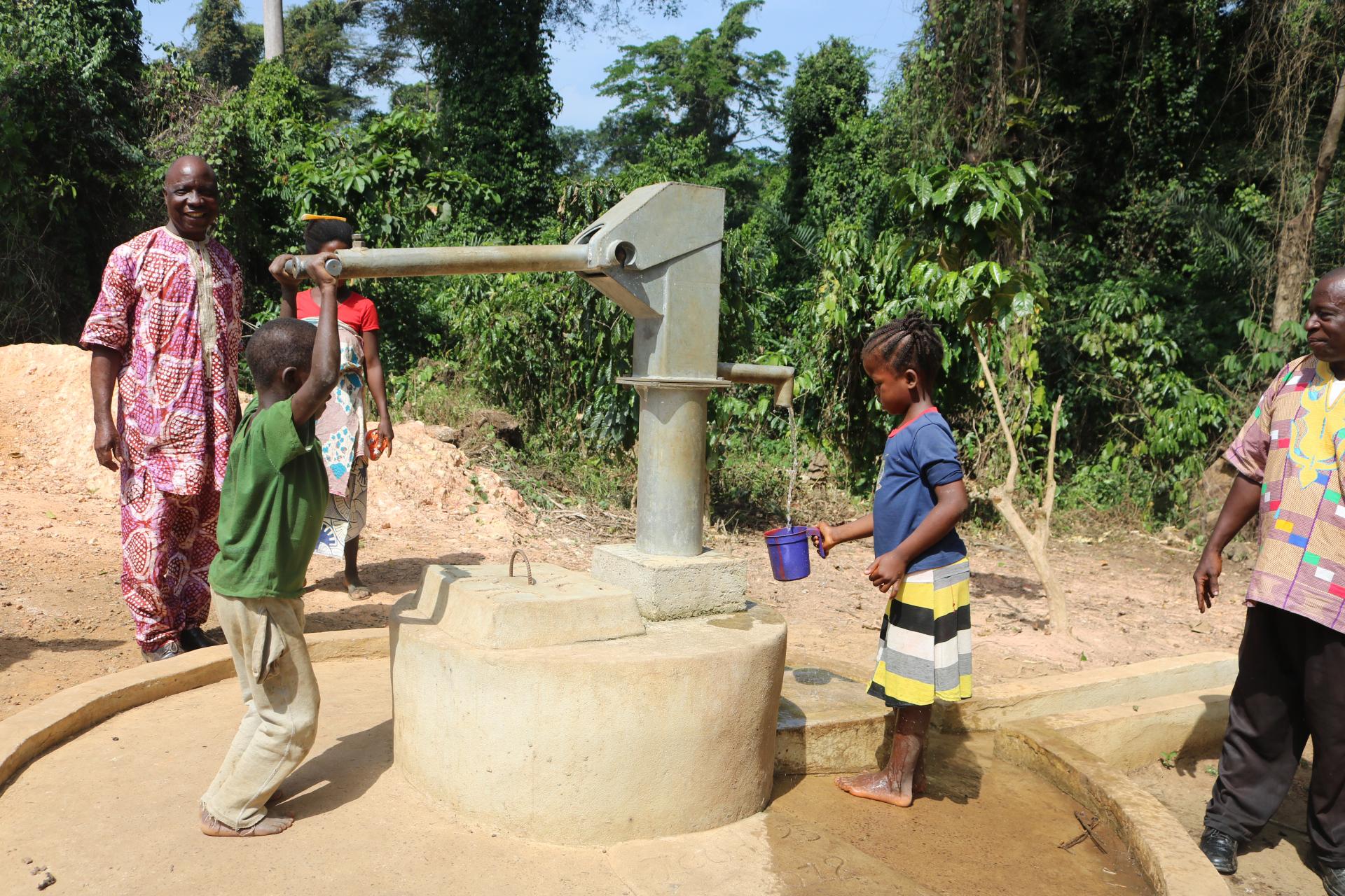 """기니아의 야싸다 지역에서, 두 아이가 어른들이 지켜보는 가운데, 우물에서 물을 퍼 올리고 있다. 리베리아 연합감리교회는 """"생명의 물"""" 프로젝트 일부로 그 지역에 5개의 우물을 파고 있다. 사진 제공 줄루 스웬, 연합감리교뉴스(UMNS)"""