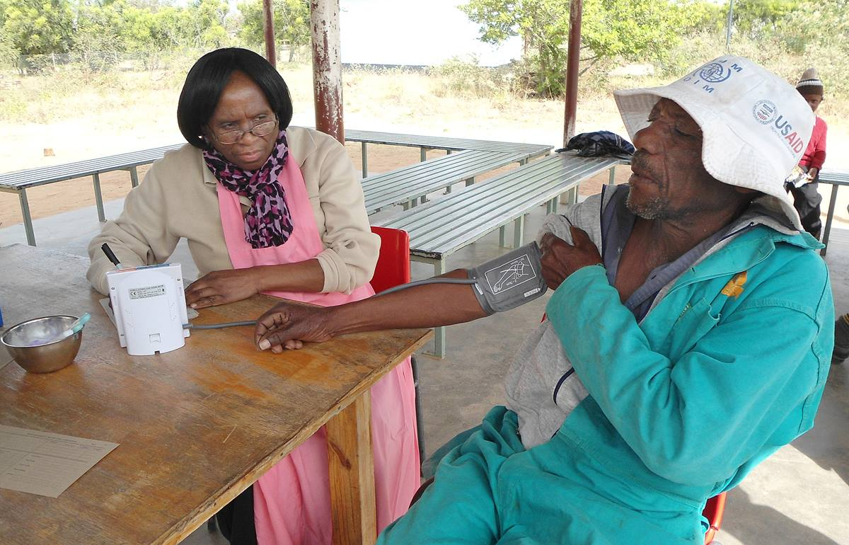Joppa Muzokomba has his blood pressure checked by Killia Jena at a mobile clinic in Marange District sponsored by the Harare East District-Chisipiti Circuit in Zimbabwe. Photo by Kudzai Chingwe, UMNS.