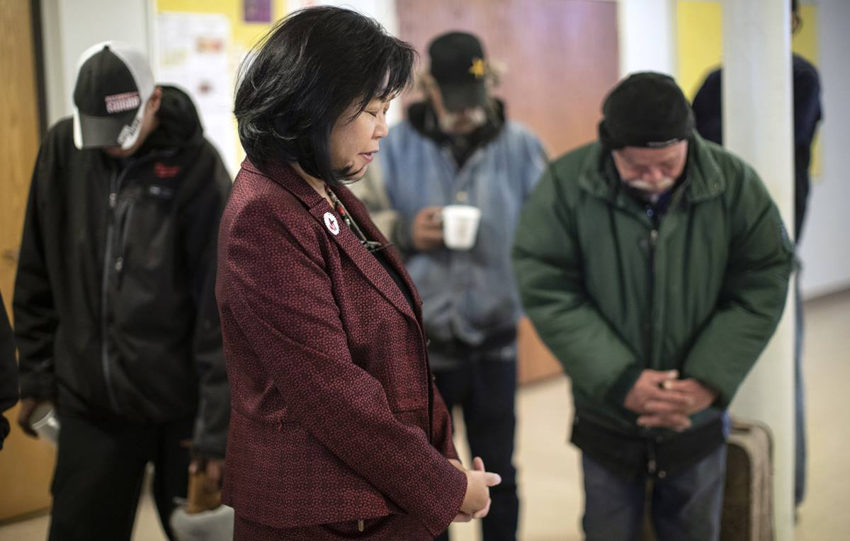 The Rev. Elizabeth McVicker, pastor of First United Methodist Church in Salt Lake City, visits and prays with the homeless during the Sunday Fellowship Breakfast. Photo by Kathleen Barry, UMNS.