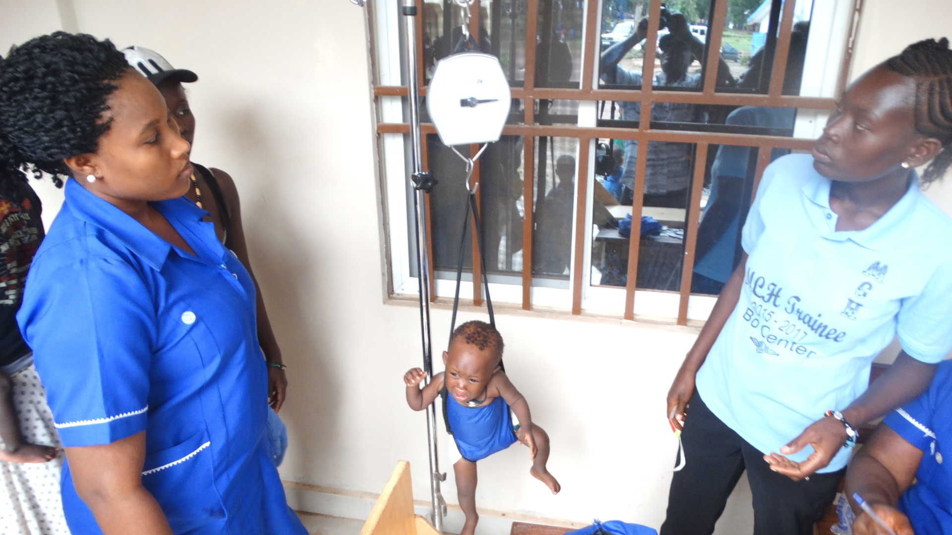Staff at United Methodist Mercy Hospital in Bo, Sierra Leone, weigh a child during one of the hospital's outreach days on the hospital grounds. Photo by Phileas Jusu, UMNS.