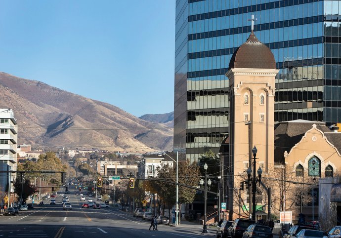 The historic church tower of First United Methodist Church in Salt Lake City contrasts with nearby modern buildings and Wasatch Mountains.
