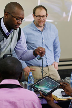 Chilima Karima and Matt Crum (standing) of United Methodist Communications instruct Roger Muzeze Tshinyemba and Francois Omanyondo Djonga in setting up their iPads during the training for Congo Central Conference communicators in Ndola, Zambia, in 2017. Agency leaders contend that a proposed 2021-24 budget cut of 37 percent is substantially more than for any other peer agency. File photo by Kathleen Barry, UMNS.