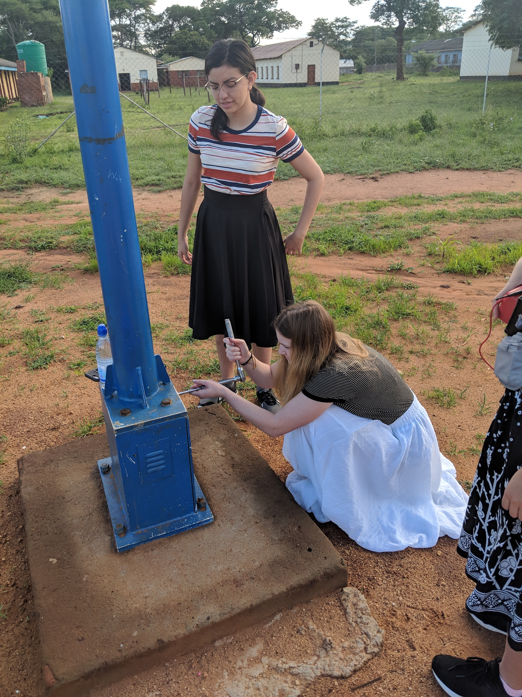Melina Driscoll and  Ashley Burbano, team members with Engineers Without Borders USA,  inspect lights at Nyadire Mission. Photo courtesy of Chenayi Kumuterera.