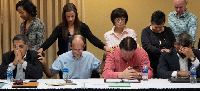 Members of the United Methodist Immigration Task Force pray with three bishops of the Methodist Church in Mexico at the beginning of the Jan. 21-23 meeting in McAllen, Texas. Mexico bishops, seated, from right, Felipe de Jesús Ruiz Aguilar, José Antonio Garza Castro (in red shirt) and Rodolfo Rivera de la Rosa (far left). Photo by Kathy L. Gilbert, UMNS.