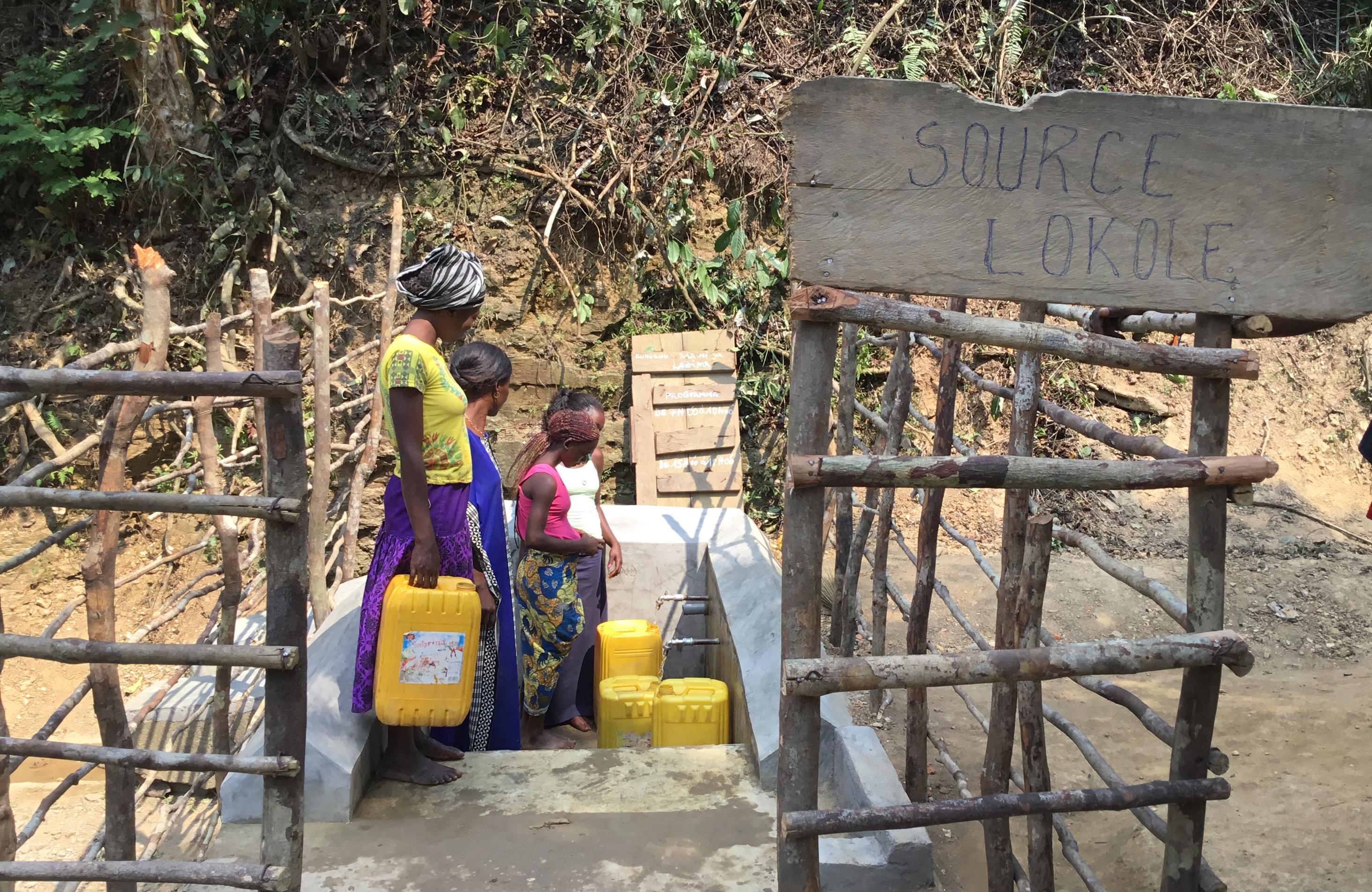 """여성들이 콩고 미켈렝게에 위치한 연합감리교회 로콜 선교회 근처의 복구된 """"로콜 우물""""에서 플라스틱 통에 물을 채우고 있다. 사진: 주디스 오송고 양가"""