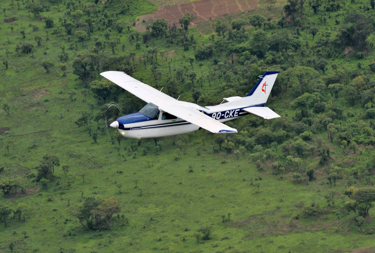 A Cessna T210 piloted by Rukang Chikomb flies through the skies over Congo in 2008. Part of the Wings of the Morning aviation ministry of The United Methodist Church, the program provides life-saving access to isolated rural communities. The photo was taken from another plane, a Cessna P210 piloted by Gaston Ntambo, that is part of the same program. File photo by Paul Jeffrey.