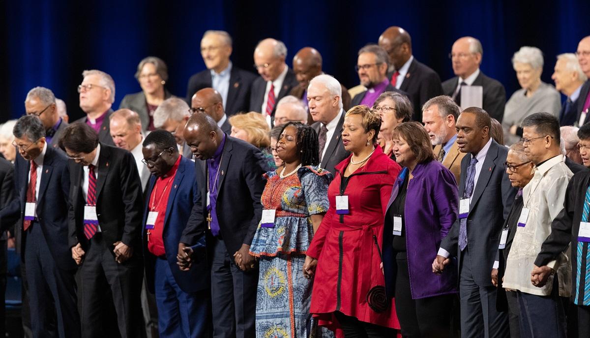 Los/as obispos/as metodistas unidos/as se dan la mano en oración durante un día de oración por la Conferencia General Metodista Unida de 2019 en San Luis. Foto Mike DuBose, SMUN.