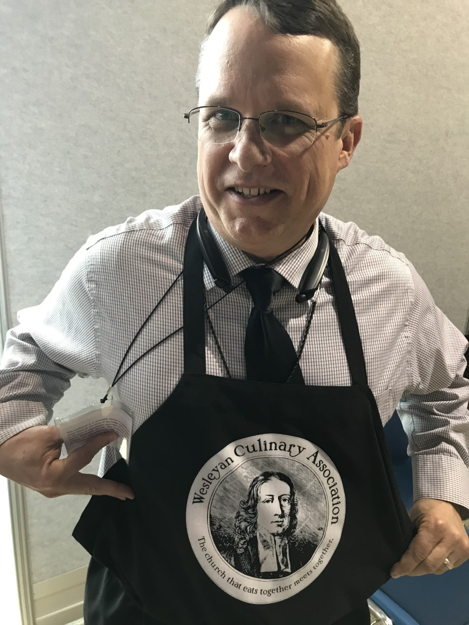 The Rev. John Feagins shows off a Wesleyan Culinary Association apron on Feb. 23. He's among many observers at the 2019 General Conference in St. Louis, and he's been in the corridors of America's Center, talking to delegates and others about how food can be a bridge for people with different theological views. The Wesleyan Culinary Association is a Facebook group which shares potluck and communion bread recipes. Photo by Sam Hodges, UMNS.