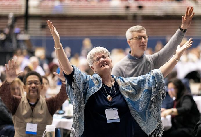 Tennessee Conference delegate Holly Neal (front) raises her arms in praise  during a day of prayer at the 2019 United Methodist General Conference in St. Louis. She is joined by Tennessee delegates the Revs. Stephen Handy (left) and Jacob Armstrong (standing). Photo by Mike DuBose, UMNS.