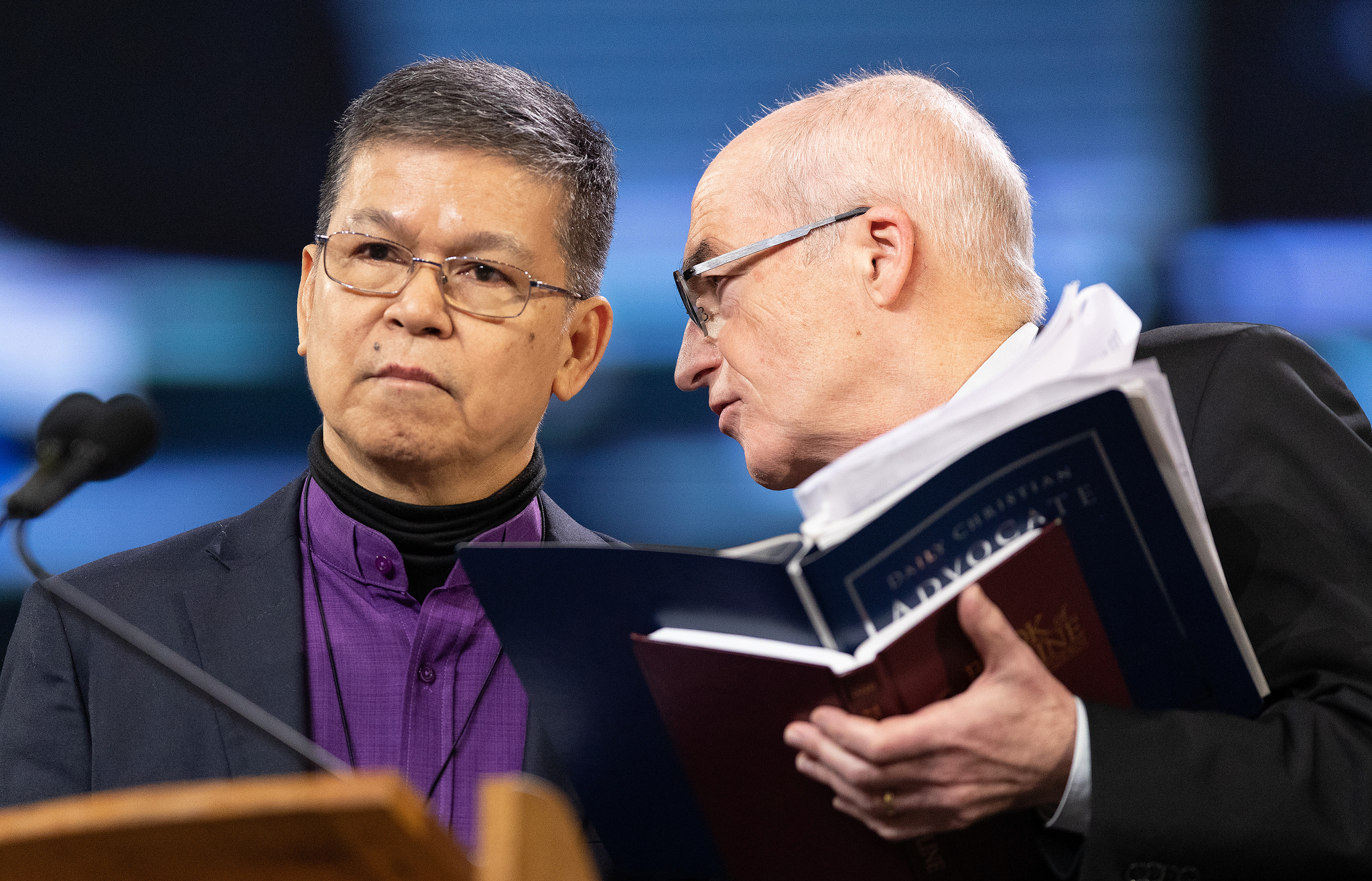 Bishops Ciriaco Q. Francisco (left) and Patrick Streiff confer at the podium during the 2019 United Methodist General Conference in St. Louis. They both serve on the Standing Committee on Central Conference Matters. Photo by Mike DuBose, UMNS.