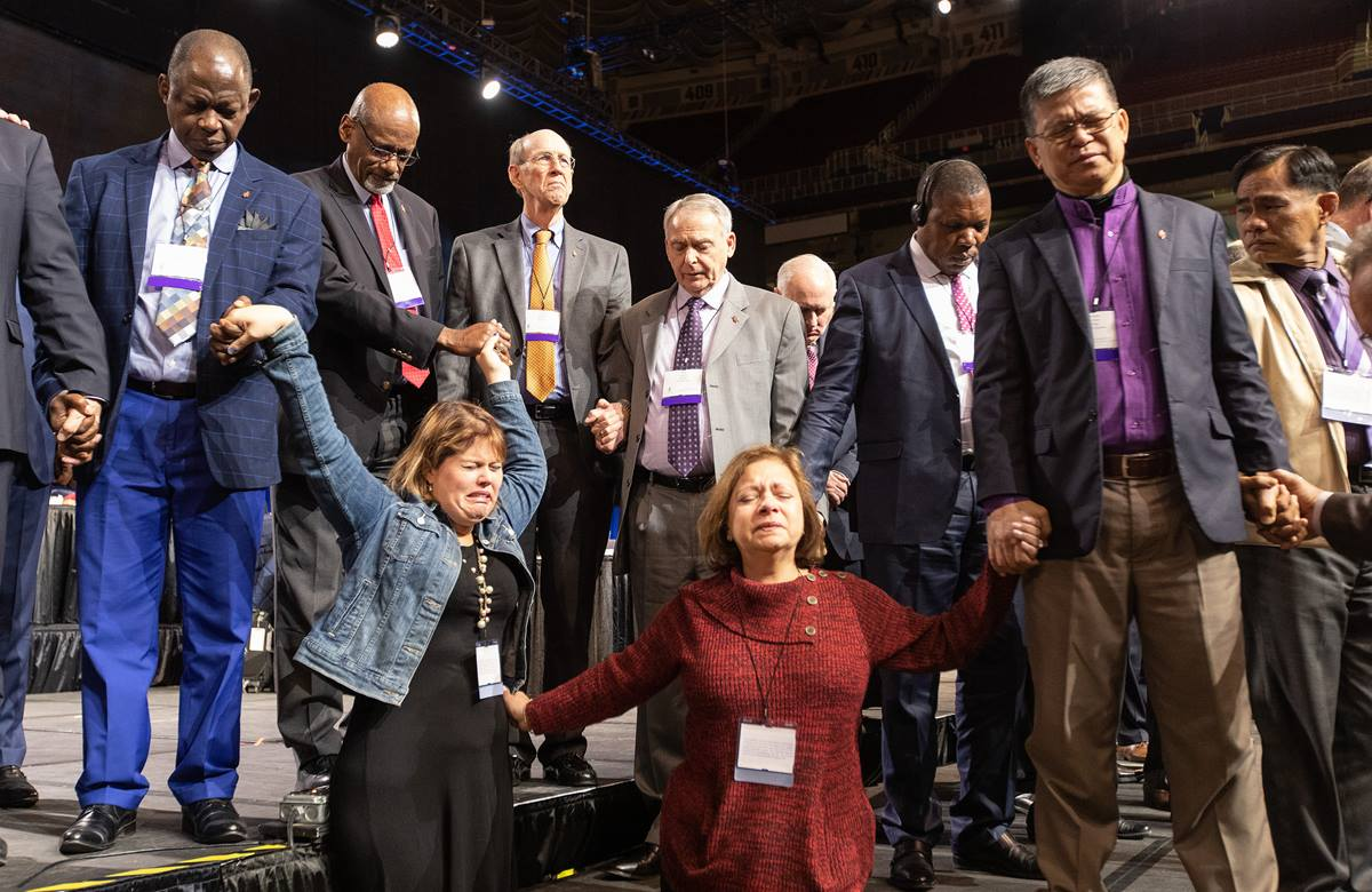 Las delegadas de Florida, Rachael Sumner (al frente en la izquierdo) y la Revda. Jacqueline Leveron (al frente en la derecha)  se unen en oración con los/as obispos/as y otros/as delegados/as al frente del presidium antes de una votación clave sobre las políticas de la iglesia en torno a la homosexualidad. Foto de Mike DuBose, SMUN.